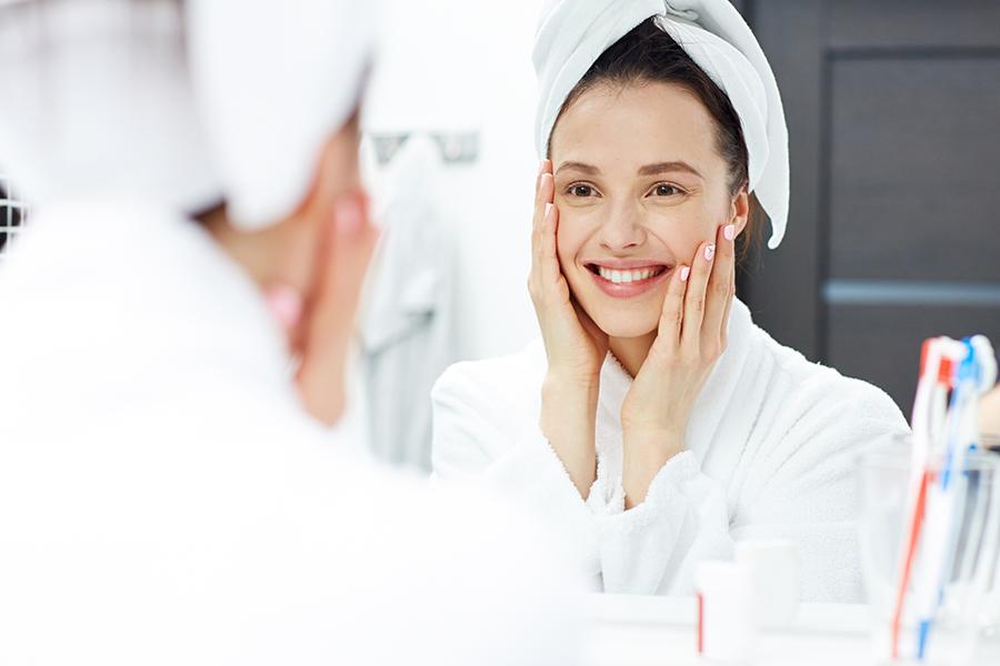 Mulher de roupão e toalha na cabeça em frente ao espelho do banheiro com alguns produtos de higiene e beleza