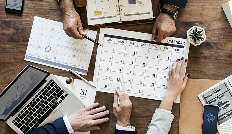 Vista de cima de uma mesa de reunião com notebook, calendários e mãos de três pessoas discutindo datas